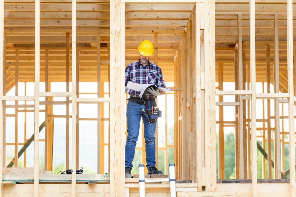 Builder reading blueprints plan of wood construction frame house