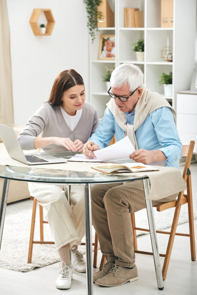 Insurance agent assisting senior to fill papers
